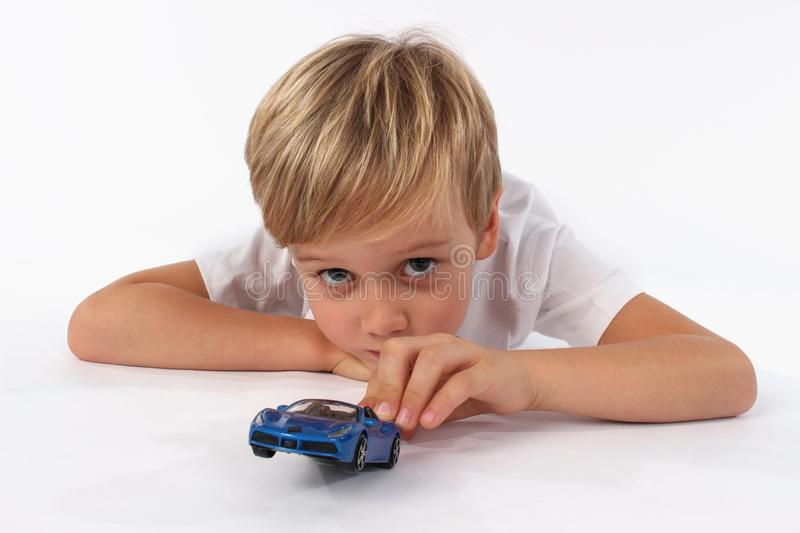 A child boy captured while playing with car toys. An adorable boy holding and pointing with a blue car toy stock image