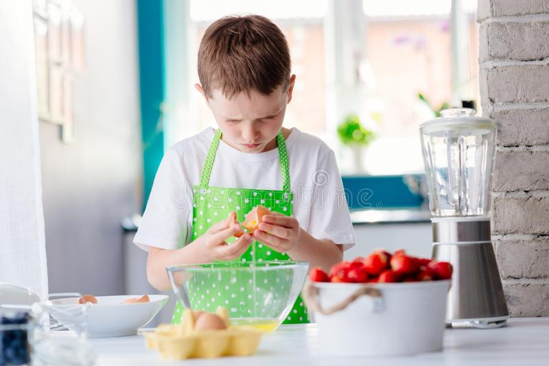 Child boy cracking egg and separating the yolk. Child helping in kitchen. Boy baking cake stock photography