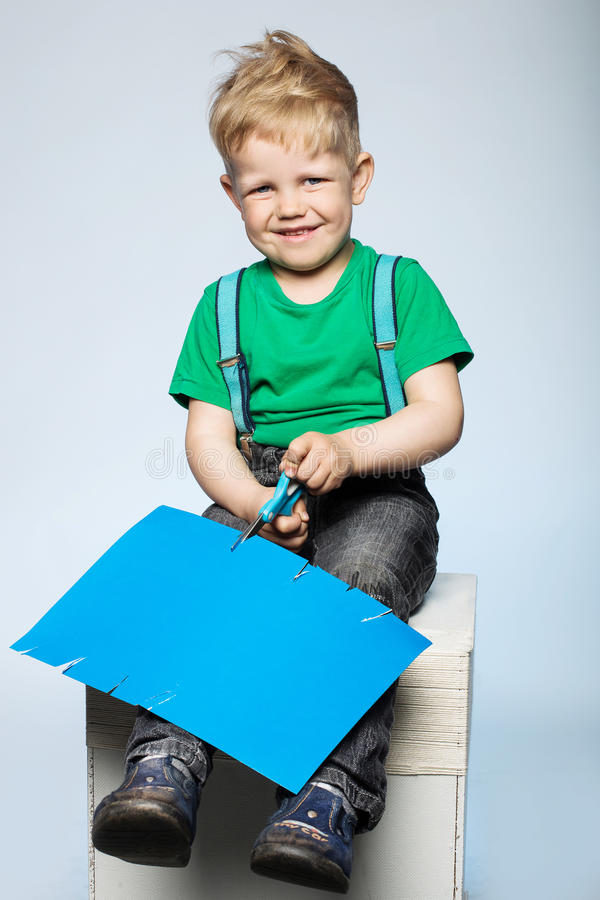 Child boy cutting colored paper with scissors royalty free stock images