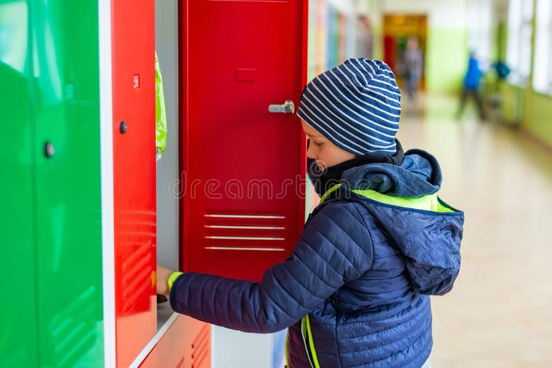 Child boy dressing his autumn jacket in school royalty free stock photography