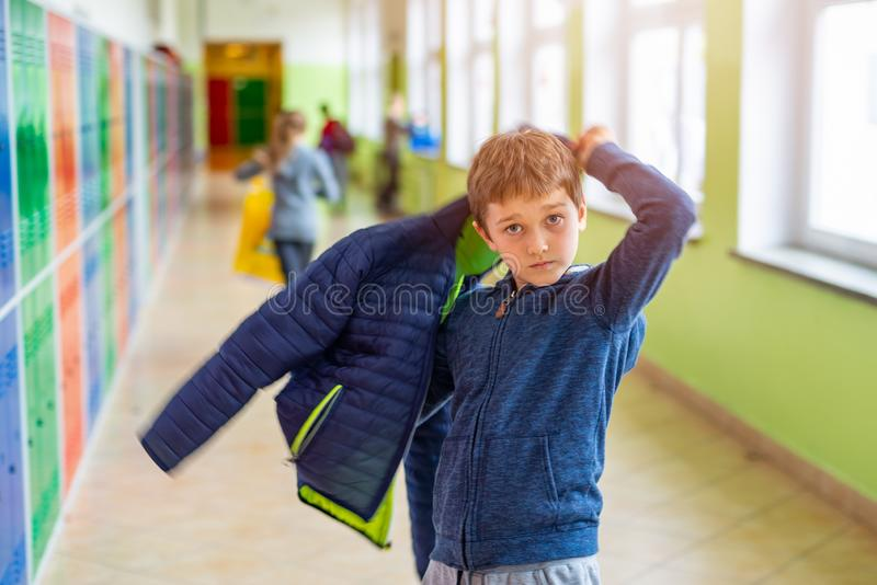 Child boy dressing his autumn jacket in school royalty free stock photo