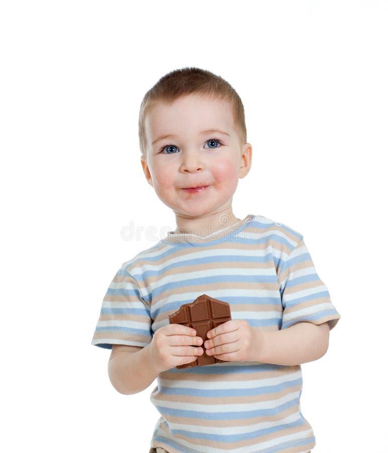 Child boy eating chocolate isolated on white royalty free stock image