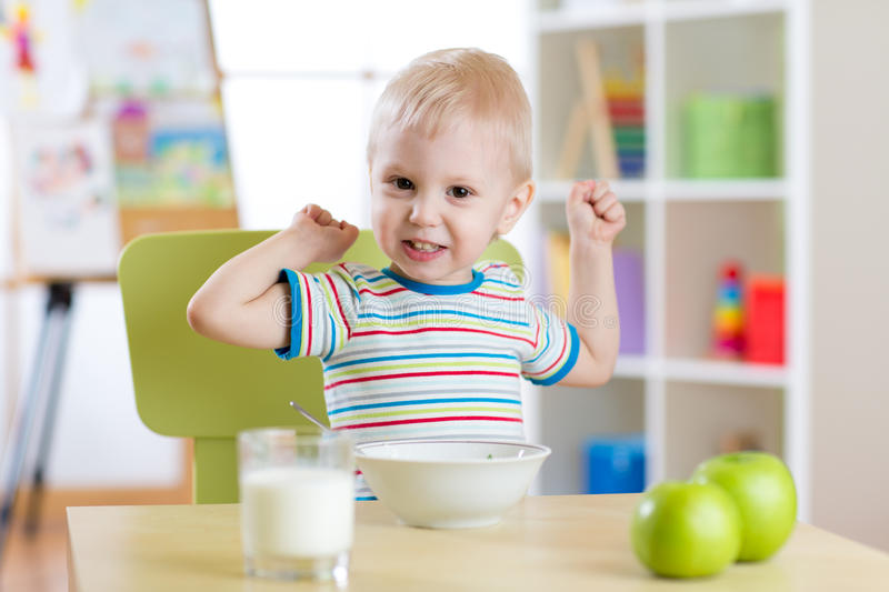 Child boy eating healthy food and showing his strength indoors. Child boy eats healthy food and showing his strength indoors royalty free stock images