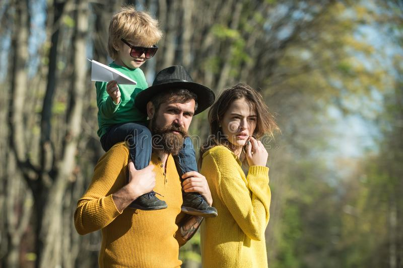 Child boy on fathers shoulder dream about flying high in forest. Little boy and family dream about travelling by plane. Lets get away from it all stock photo