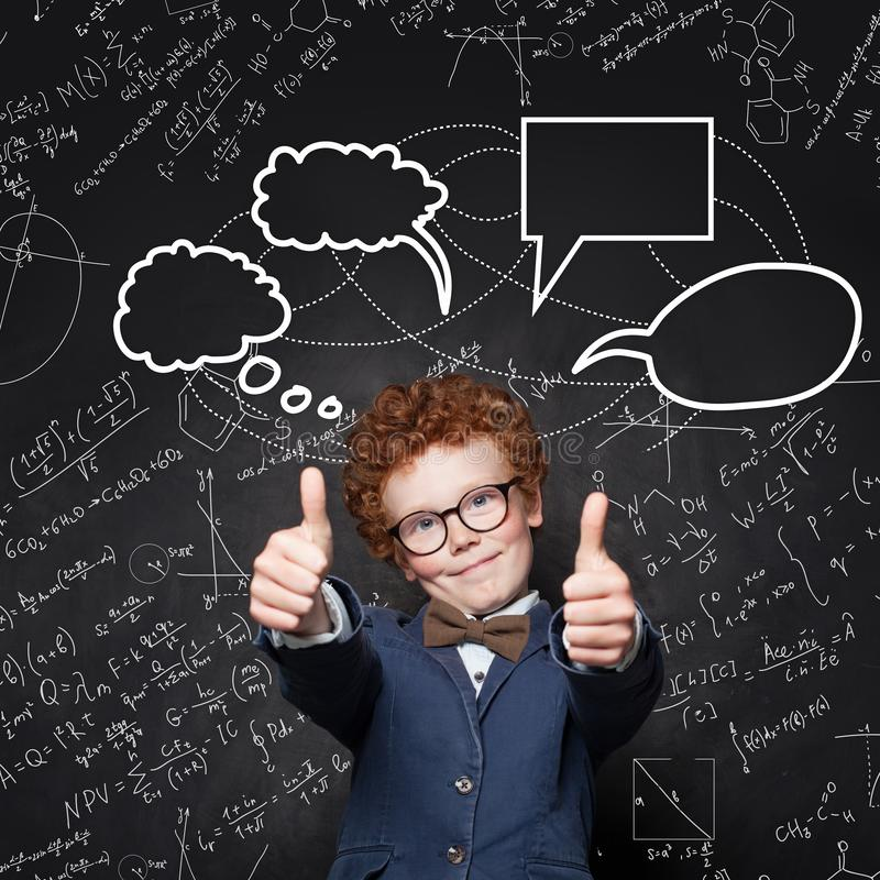 Child boy with ginger hair showing thumb up on blackboard background. Smart kid in glassed with science  formulas stock photography
