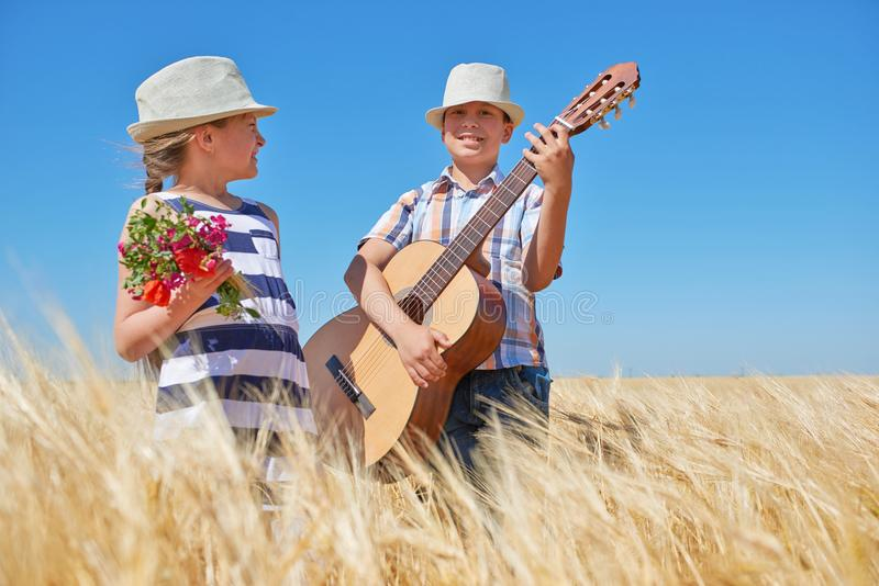 Child boy and girl with guitar are in the yellow wheat field, bright sun, summer landscape royalty free stock images