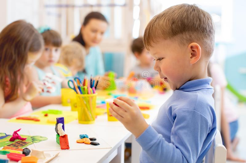 Child boy and group of kids working with colorful clay toy at nursery or kindergarten royalty free stock photo