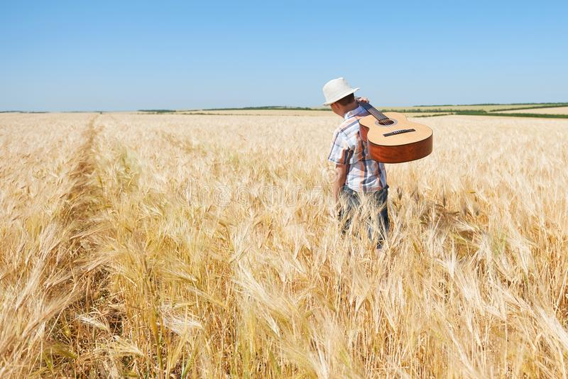 Child boy with guitar is in the yellow wheat field, bright sun, summer landscape stock photo