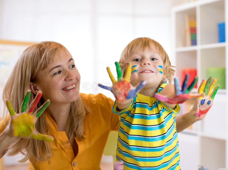 Child boy and his mom with painted hands. Kid drawing and coloring with teacher in daycare center or playschool. Child boy and his mother with painted hands stock photo