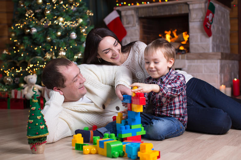 Child boy and his parents playing with block toys under the christmas tree stock photo