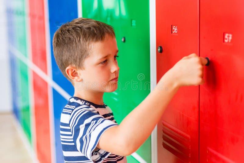 Child boy opening metal school locker. royalty free stock images