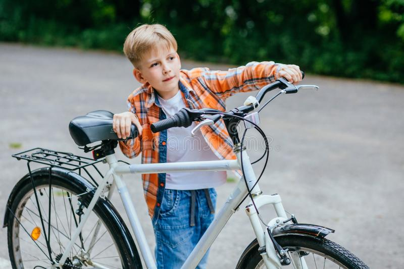 Child boy in orange shirt carries a big bike in the summer park outdoor royalty free stock photos