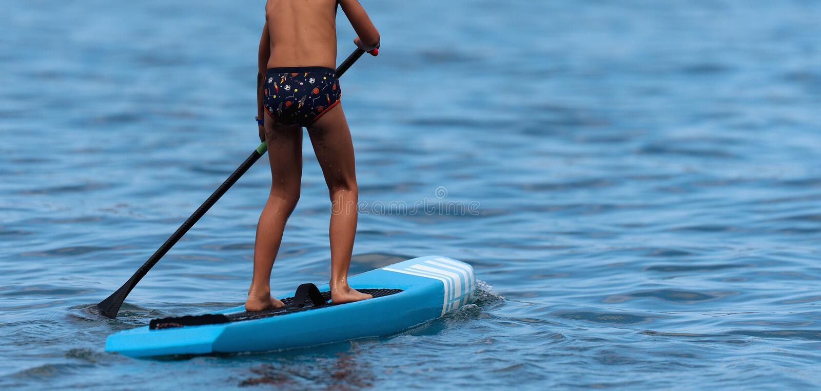 Child boy paddling on stand up paddle board stock images