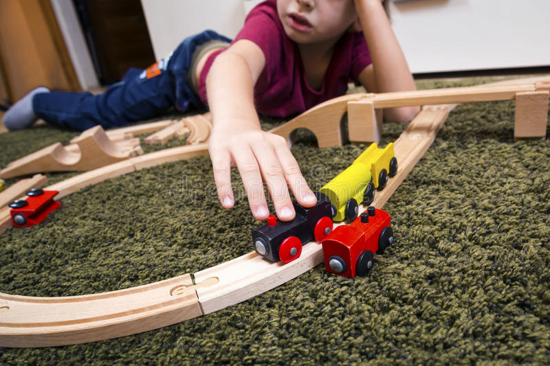 Child boy play with wooden train, build toy railroad at home or stock photo