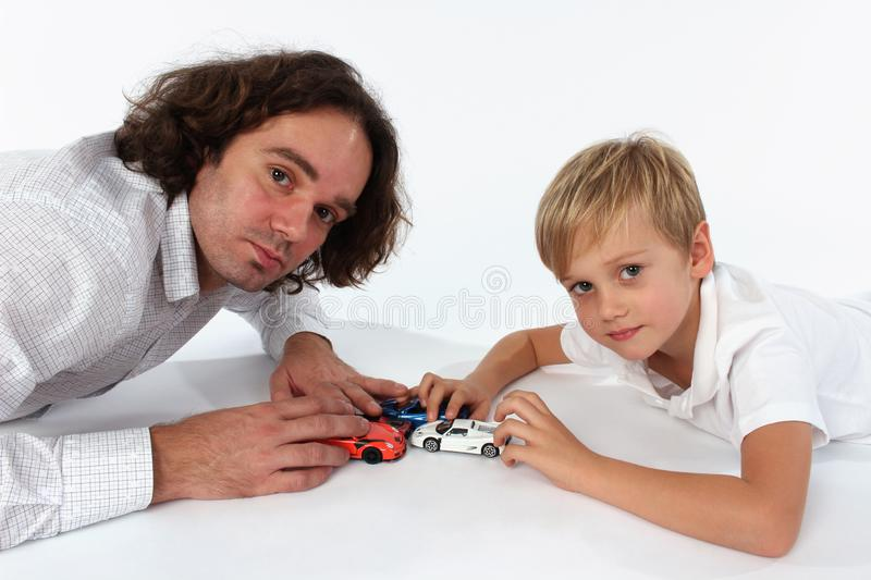 A child boy playing with car toys with his daddy. A family time where a father is playing with his son. Playtime for children stock photo