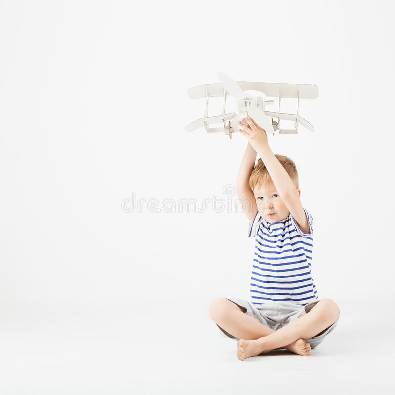Child boy playing with paper toy airplane and dreaming of becoming a pilot against a white background. Child boy playing with paper toy airplane sitting on the royalty free stock image