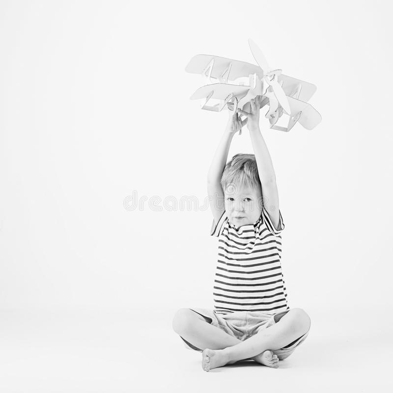 Child boy playing with paper toy airplane sitting on the floor a. Gainst a white background. Kid dreaming of becoming a pilot. Black and white photography stock photos