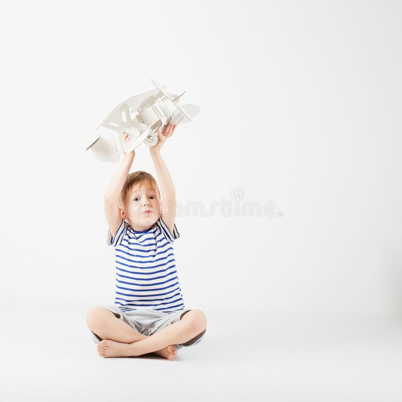 Child boy playing with paper toy airplane sitting on the floor a. Gainst a white background. Kid dreaming of becoming a pilot. Childhood. Fantasy, imagination stock image