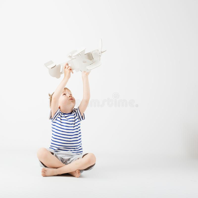 Child boy playing with paper toy airplane sitting on the floor a. Gainst a white background. Kid dreaming of becoming a pilot. Childhood. Fantasy, imagination stock photos