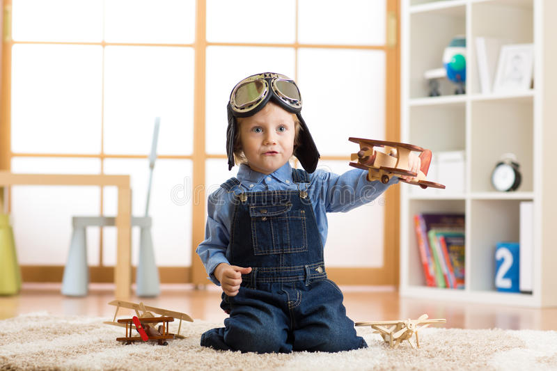 Child boy pretending to be pilot. Kid playing with toy airplanes at home. Travel and dream concept. Child boy pretending to be pilot aviator. Kid playing with stock photos