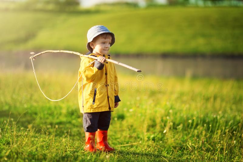 Child boy ready for fishing. Cute little boy in hat holding big fishing net at the ready. Summer vacation concept royalty free stock images
