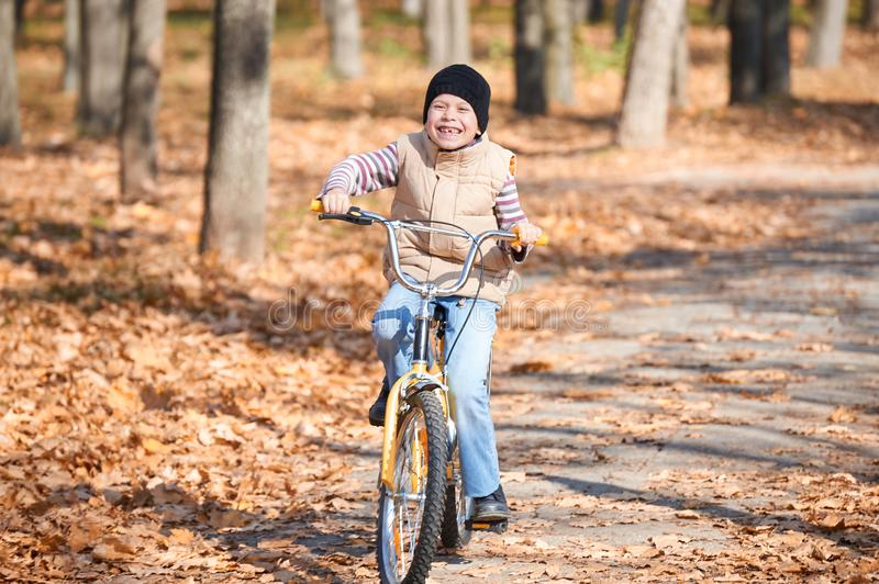 Child boy riding on Bicycle in autumn Park, bright sunny day, fallen leaves on background stock images