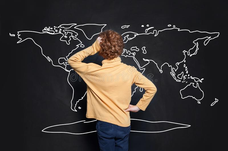 Child boy student looking at map of Earth on chalkboard background and learning geography.  stock photos