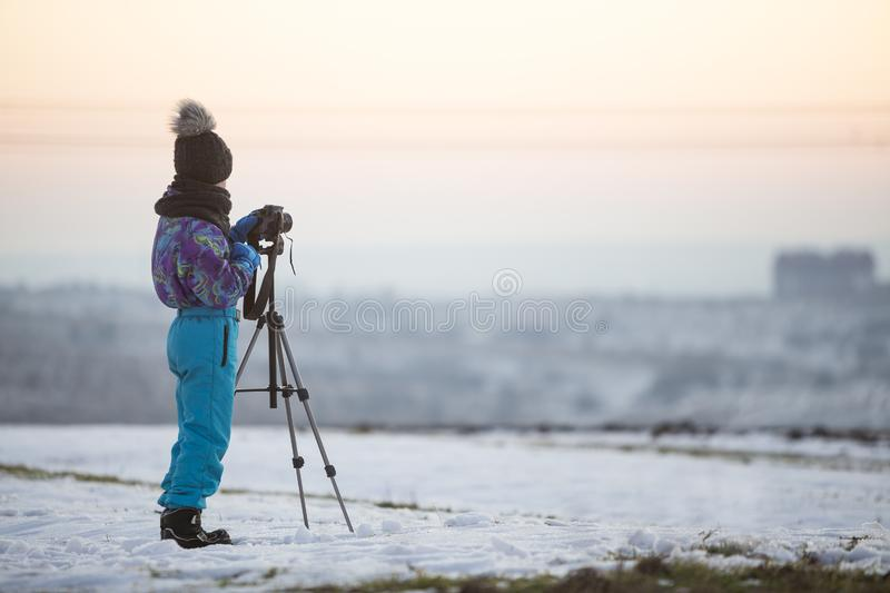 Child boy taking pictures outside in winter with photo camera on a tripod on snow covered field royalty free stock photo