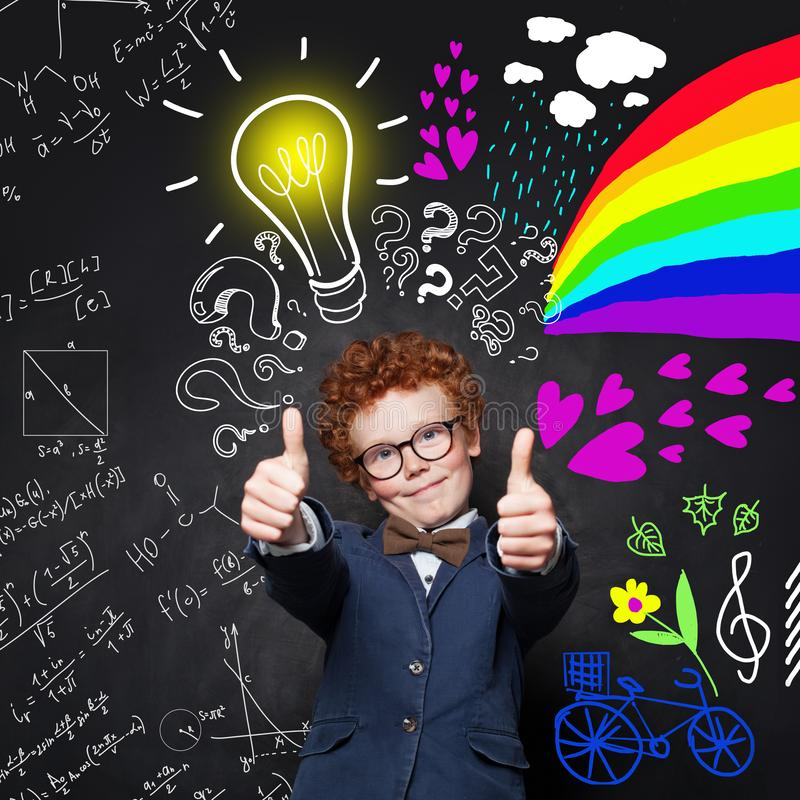 Child boy with thumbs up having fun on science and arts background. Light bulb brainstorming and idea concept royalty free stock images