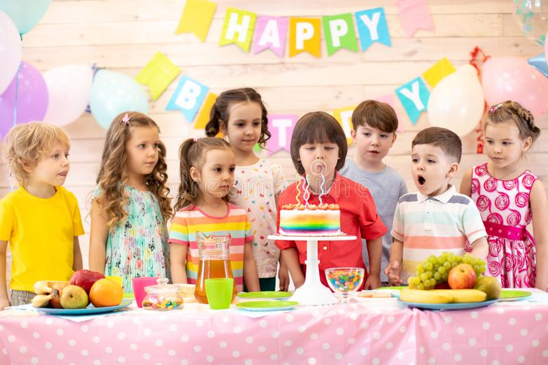 Child boy blowing the candles of its cake of birthday. Child boy together with friends blowing the candles of its cake of birthday. Group of kids on party in royalty free stock photo