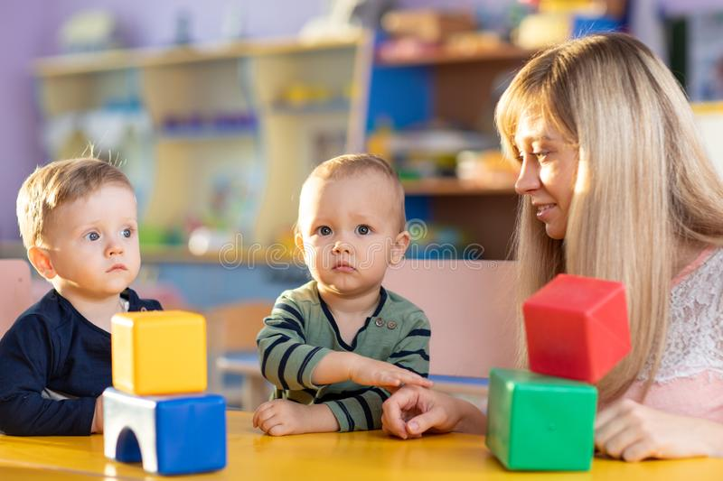 Child boy together with mother playing educational toys at sunny day in nursery stock photo