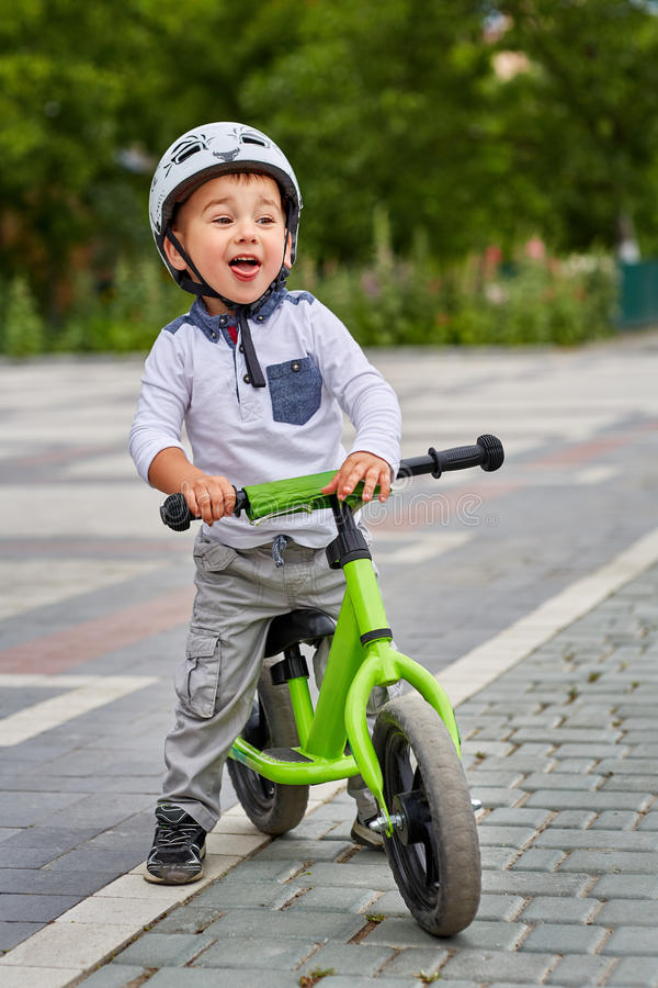 Child boy in white helmet riding on his first bike with a helmet. Bike without pedals. royalty free stock photo