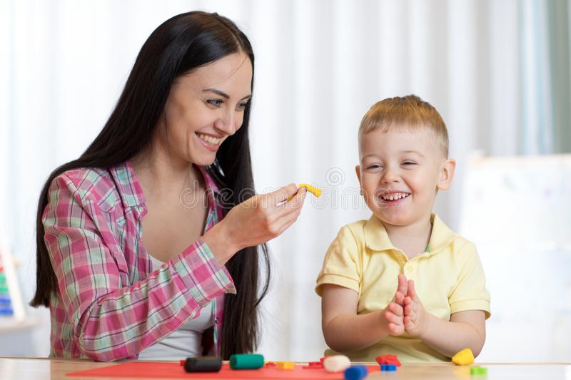 Child boy and woman play colorful clay toy at nursery or kindergarten royalty free stock photo