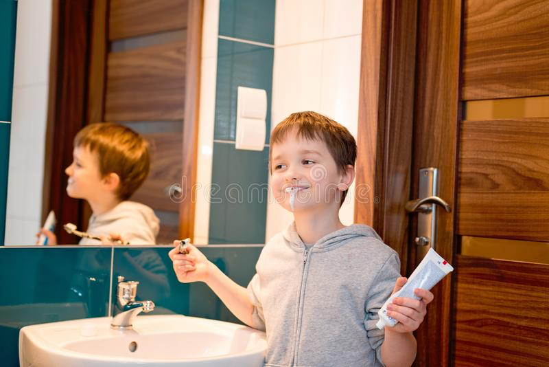 Child brushing his teeth in the bathroom. stock photo