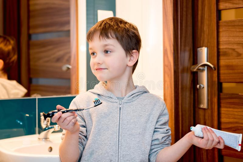 Child brushing his teeth in the bathroom. stock images