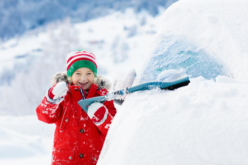 Child brushing off car. Kid with winter snow brush stock photos