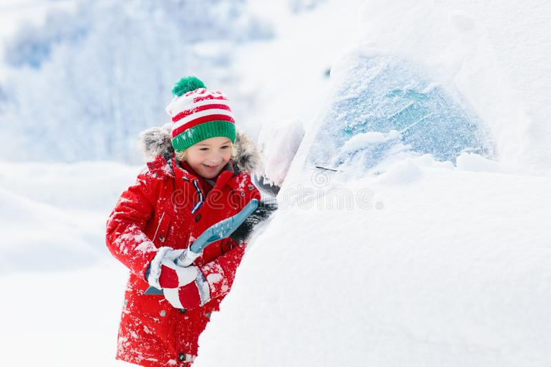 Child brushing snow off car after storm. Kid with winter brush and scraper clearing family car after overnight snow blizzard. royalty free stock photos