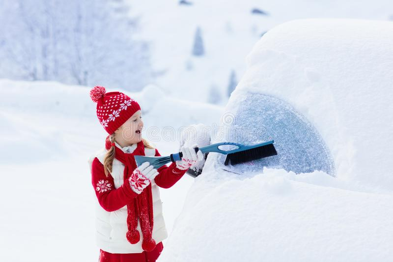 Child brushing snow off car after storm. Kid with winter brush and scraper clearing family car after overnight snow blizzard. Family Christmas vacation in the stock photography