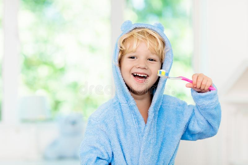 Child brushing teeth. Kids tooth brush. And paste. Little baby boy in blue bath robe or towel brushing his teeth in white bathroom with window on sunny morning stock photo