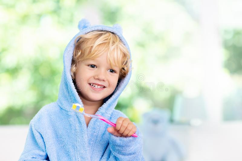 Child brushing teeth. Kids tooth brush. And paste. Little baby boy in blue bath robe or towel brushing his teeth in white bathroom with window on sunny morning stock image