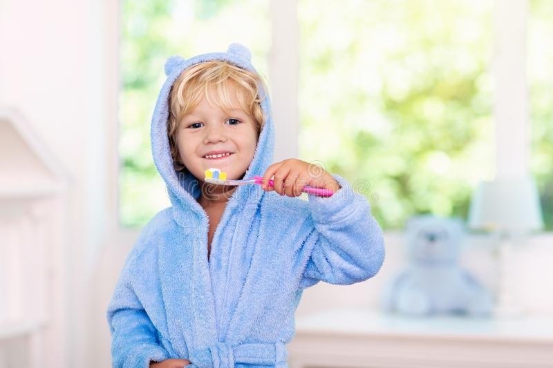Child brushing teeth. Kids tooth brush. And paste. Little baby boy in blue bath robe or towel brushing his teeth in white bathroom with window on sunny morning stock photos
