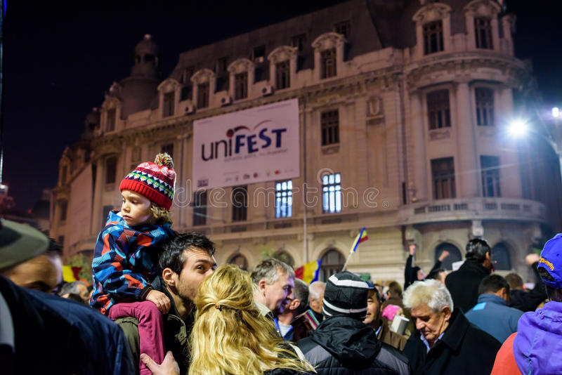 Child at Bucharest 2015 demonstrations. A child on the shoulders of a man at the demonstration demanding end to the corruption and to the incompetence of the royalty free stock photos