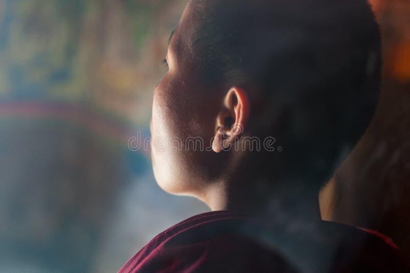 Child buddhist monk praying in monastery, Tibet stock photo