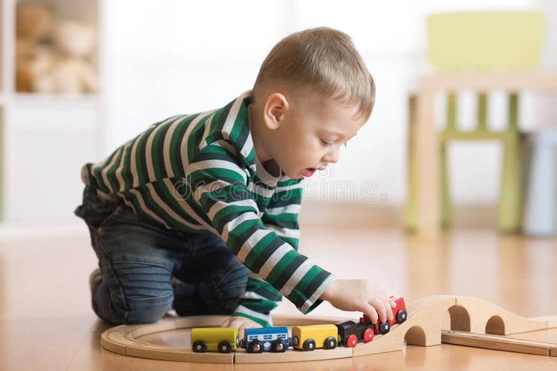 Child building and playing toy railroad at home or daycare. Toddler boy play with train and cars. royalty free stock photos