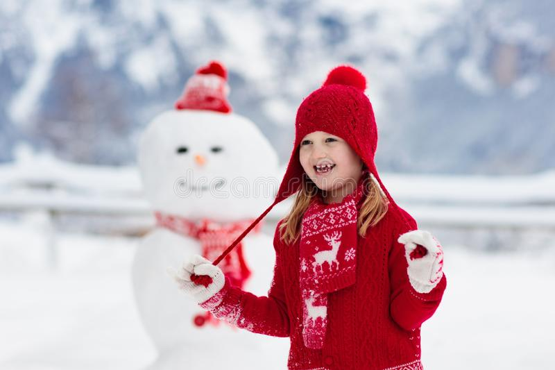 Child building snowman. Kids build snow man. Boy and girl playing outdoors on snowy winter day. Outdoor family fun on Christmas stock photography