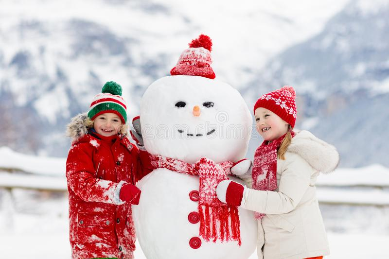 Child building snowman. Kids build snow man. Boy and girl playing outdoors on snowy winter day. Outdoor family fun on Christmas. Vacation in the mountains royalty free stock photo