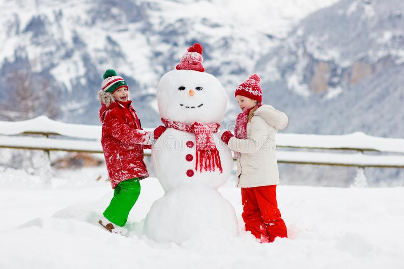 Child building snowman. Kids build snow man. Boy and girl playing outdoors on snowy winter day. Outdoor family fun on Christmas stock photos