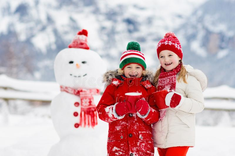 Child building snowman. Kids build snow man. Boy and girl playing outdoors on snowy winter day. Outdoor family fun on Christmas stock image