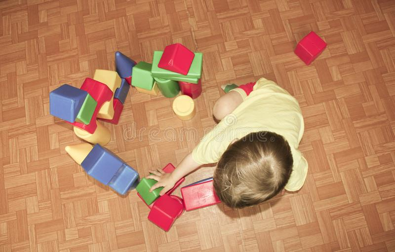The child builds a castle out of plastic designer. A little boy stock images