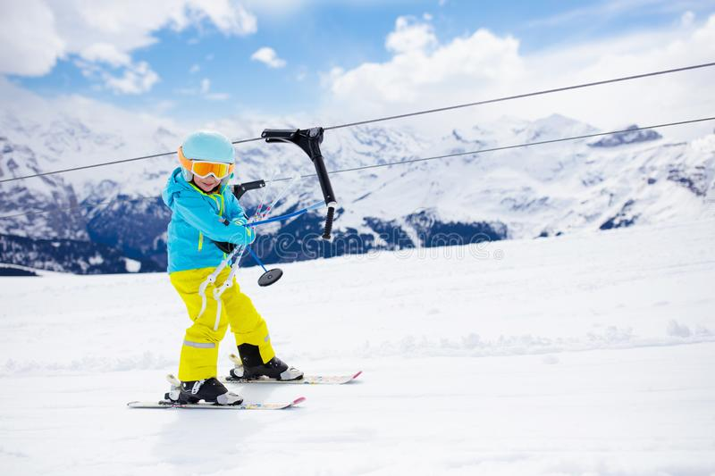 Ski and snow winter fun for kids. Children skiing. Child on a button ski lift going uphill in the mountains on a sunny snowy day. Kids in winter sport school in stock image